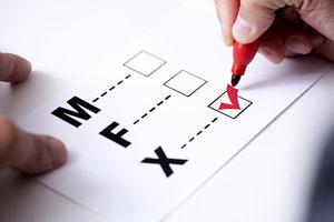 Das Bild zeigt ein Formular mit drei Geschlechteroptionen: M, F und X. Eine Hand mit einem roten Stift setzt ein Kreuz bei X.