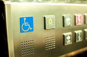 Das Bild zeigt das Bedienfeld eines Aufzugs mit einem Piktogramm für Rollstuhlfahrer*innen..